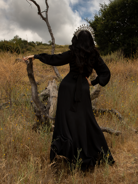 Looking away from the camera and up at grey skies, Micheline Pitt gives us a look at the back of the Opera Satin Gown in Black.