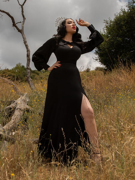 Standing against a grey skies in a field with dead trees, Micheline Pitt models the goth style Opera Satin Gown in Black.