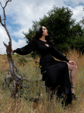 Sat on a downed tree we get a profile shot of Micheline Pitt while she wears the Opera Satin Gown in Black from La Femme en Noir.