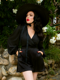 Micheline Pitt looking off camera while wearing a black sunhat along with matching black flowy top and crepe satin shorts.