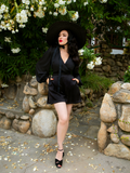 Full body shot of Micheline Pitt standing and posing in a lush garden while wearing the Opera Black Crepe Satin Shorts from La Femme en Noir