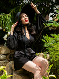 Micheline Pitt sitting on stones in a garden setting wearing a gothic retro inspired outfit featuring Opera Black Crepe Satin Shots.