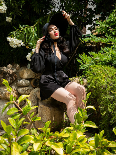 Micheline Pitt sitting in a green, lavish garden while wearing an all black outfit including sunhat, flowy top, and Opera Black Crepe Satin Shorts.