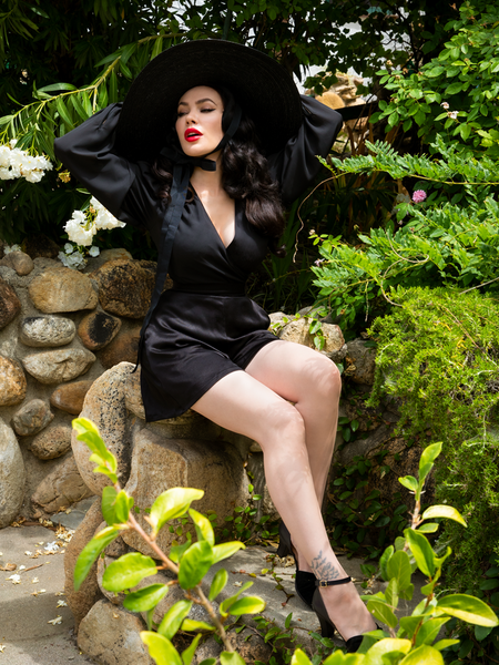 Posing while sitting on rocks in her garden, Micheline Pitt shows off the gothic retro style Opera Black Crepe Satin Shorts.