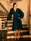 Aliza standing on a wooden stairway with her hand in the pocket of her Serpentine Wrap Dress in Green Snake Print.