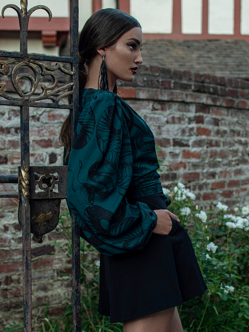 Aliza leaning against an ornate rod iron gate while modeling a goth style outfit.