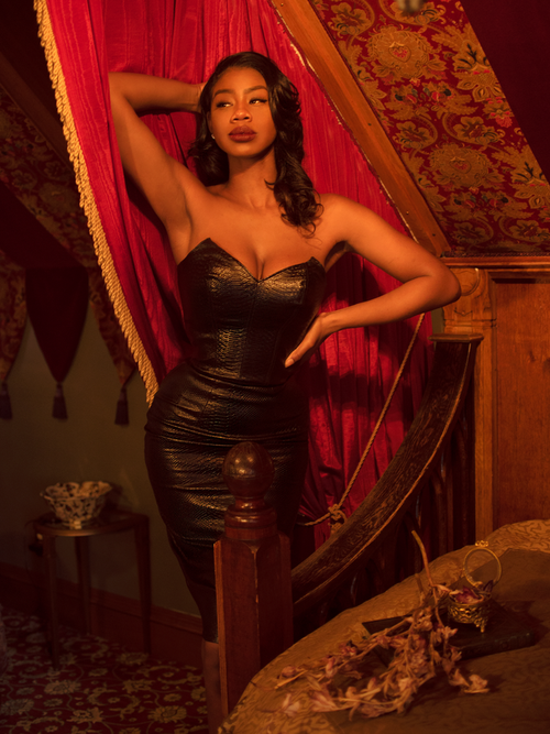 A stylized photo of Chelsea in a romantic boudoir modeling the Serpentine pencil skirt in vegan leather.