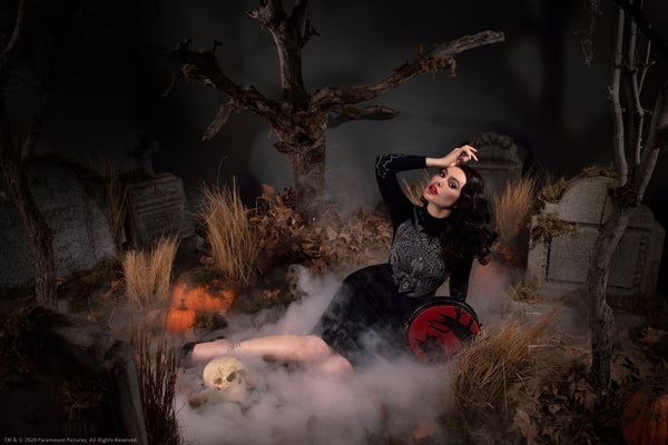 Micheline Pitt posed in a a foggy graveyard scene with the Sleepy Hollow Headless Horseman Crossbody Bag in Black and Red.
