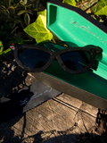 Product shot of the Serpent Sunglasses in Black sitting on top of the open coffin-shaped carrying case and next to the branded cleaning cloth.