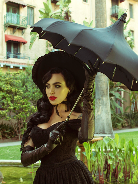 Micheline Pitt stands in a garden holding a black umbrella while modeling the Southern Gothic bustier top in black.
