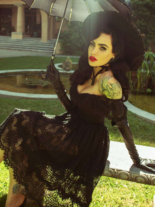 Micheilne Pitt sitting on a stone bench holding a black parasol models a gothic inspired outfit from La Femme en Noir.