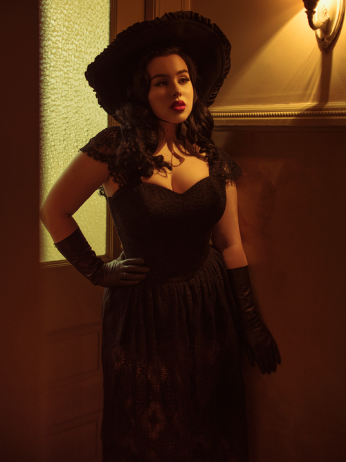 A photo of Rachel in a dark hallway modeling the Southern Gothic skirt in black petite.