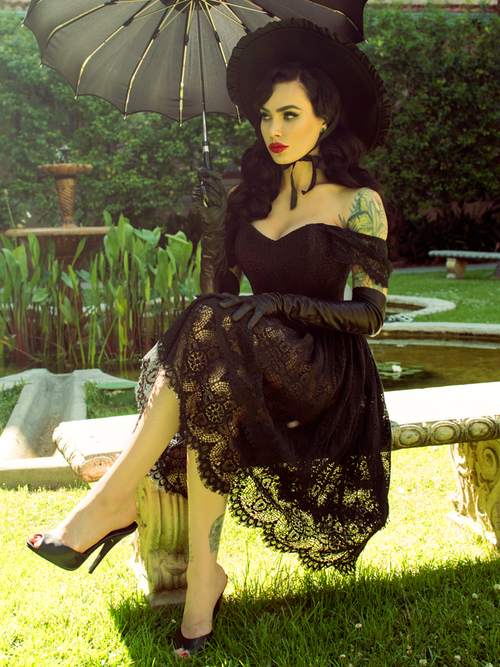 Micheline Pitt sitting in a lush and quaint garden area wearing the Southern Gothic Skirt in Black while sitting on a stone bench.