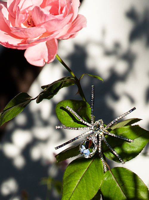 Black widow rhinestone spider brooch sitting on the leaves of a pink rose.