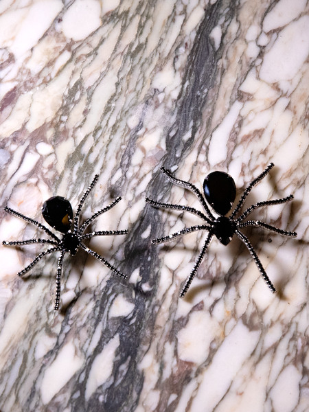Two of the Black Widow Rhinestone Spider Brooches sitting next to each other on granite countertop.