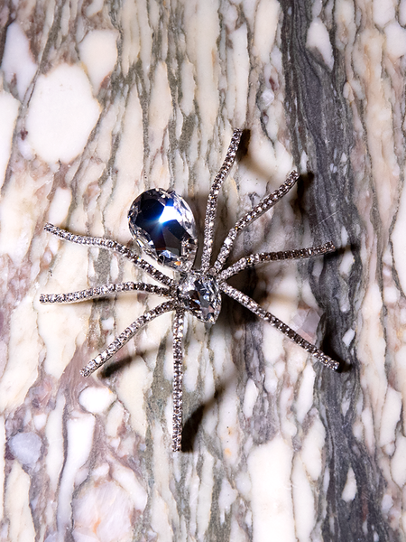 Pictured on top of a granite slab, the Spider Baby Rhinestone Brooch from La Femme en Noir.