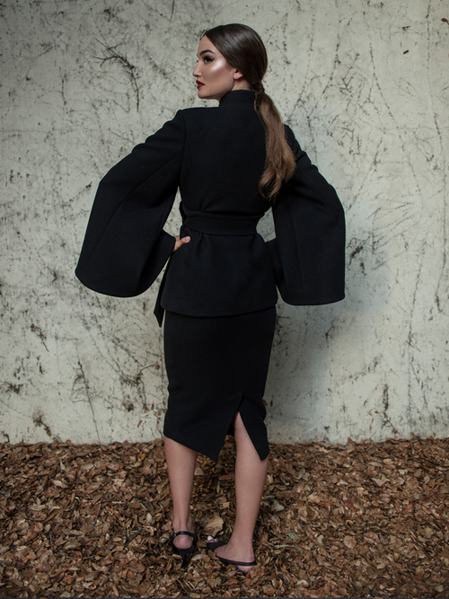 Aliza turned away from the camera to show off the back of the Metropolis Suit Skirt in Black from La femme en Noir.