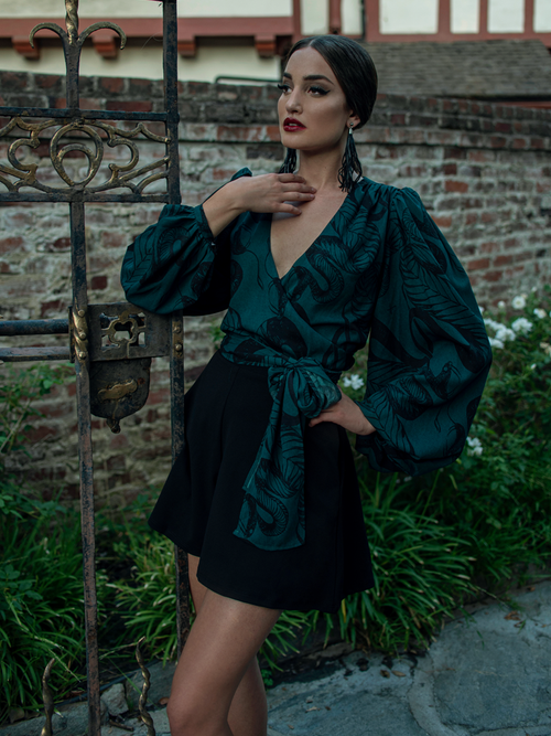 Aliza wearing the Georgette Wrap Blouse in Serpentine Print by Natalie Hall while hanging onto a rod iron vintage gate.