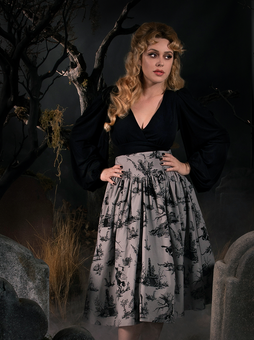 Linda standing in a spooky graveyard wearing the Sleepy Hollow Gothic Tales Toile Skirt in Grey.