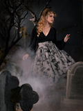 Linda swaying in a graveyard while wearing a gothic vintage outfit including a flowy black longsleeve top and Sleepy Hollow Gothic Tale Toiles Skirt in Grey.