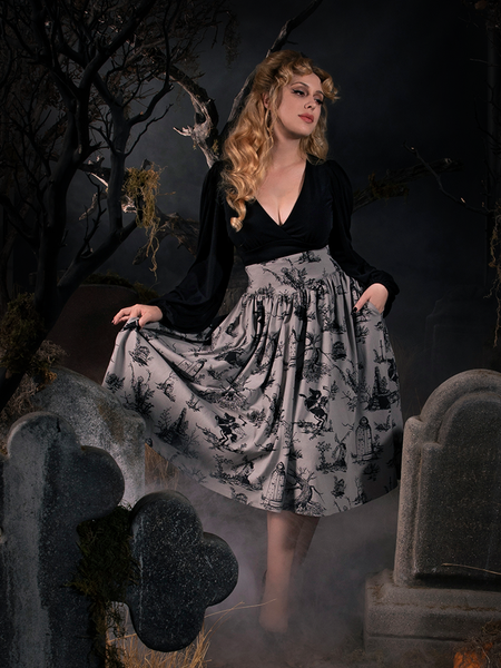 Linda showing off her gothic retro clothing outfit while standing in a foggy graveyard amongst tombstones.