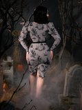 Rachel turned away from the camera to show off the back of the Sleepy Hollow Gothic Tales Toile Wiggle Dress in Grey from La Femme en Noir.