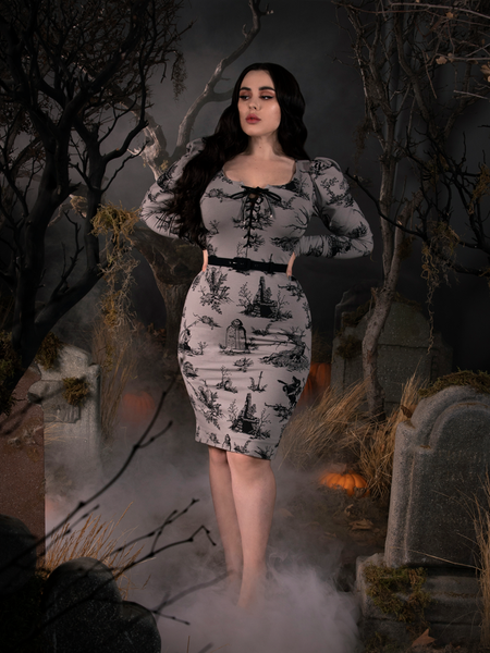 Rachel Sedory with her hands on her waist poses in the Sleepy Hollow Gothic Tales Toile Wiggle Dress in Grey.