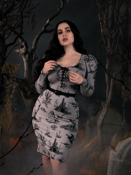 Model Rachel Sedory standing in a foggy cemetery wearing a grey goth dress inspired by Sleepy Hollow.