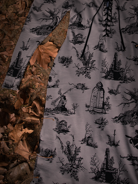 Close up of the Sleepy Hollow Gothic Tales Toile Wiggle Dress in Grey laying flat on a bed of leaves.