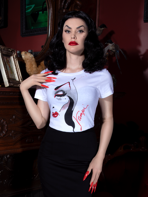 Heather, with her hand on her shoulder, models the women's Vampira white t-shirt from La Femme En Noir.