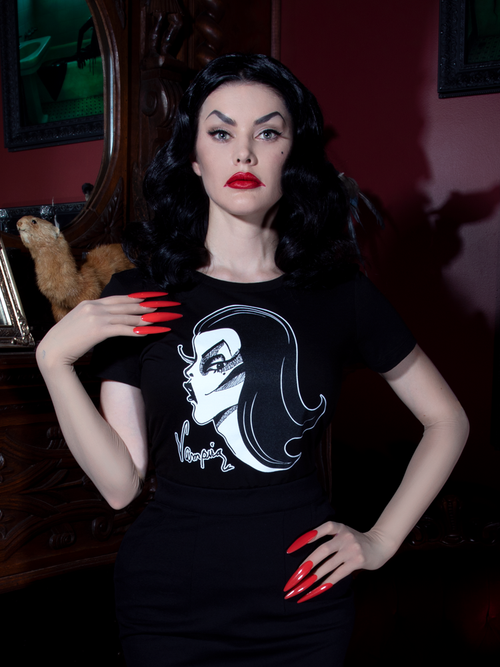 Heather, looking at the camera with her hand on her shoulder, models the women's Vampira t-shirt.