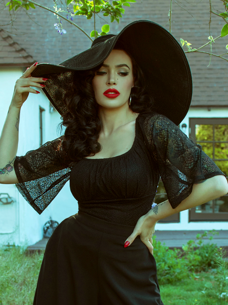 Posing with one hand on her hip and another on her black sunhat, Micheline Pitt wears the Wicked Web Top in Black from La Femme Noir.