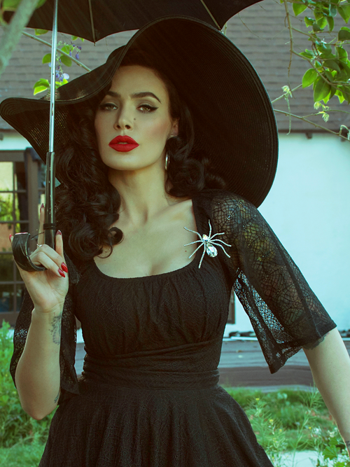 Holding a black umbrella, Micheline Pitt wears the Wicked Web Top in Black featuring a webbed sleeves and intricate stitch design.