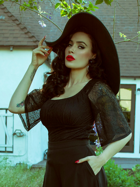 Posing with a hand in her pocket and one on the brim of her black sunhat, Micheline Pitt stares directly into the camera while wearing a glamorous gothic spiderweb top from La Femme Noir Clothing.