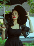 Micheline Pitt posing in a garden wearing a black sunhat and gothic webbed black top