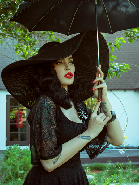 Innocently looking off-camera, Micheline Pitt models the Wicked Web Top in Black from La Femme Noir Clothing.