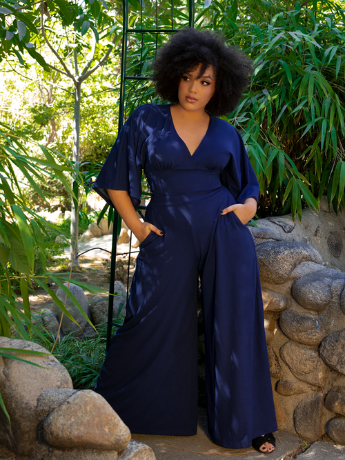 Ashleeta posing in an outdoor garden while modeling the Black Widow Palazzo Pants in Navy along with a matching flowy long sleeve top.