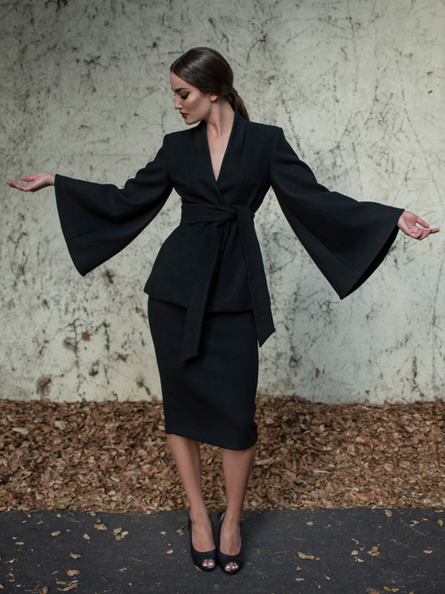 Aliza wearing the Metropolis Suit Skirt in Black while standing in front of a concrete wall.