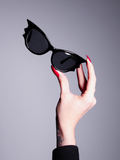 The Vamp Batwing Sunglasses being held up by a fair skinned hand with long red nails.