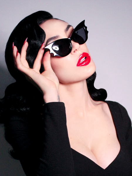 Micheline Pitt showing off her gothic retro outfit that includes the Vamp Batwing Sunglasses in Black.
