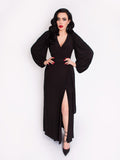 Micheline Pitt standing in front of a white backdrop modeling the all black Black Widow Wrap Gown in Solid Black