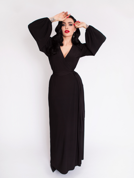 Micheline Pitt standing and posing with her hands positioned on her face while wearing the Black Widow Wrap Gown in Solid Black.