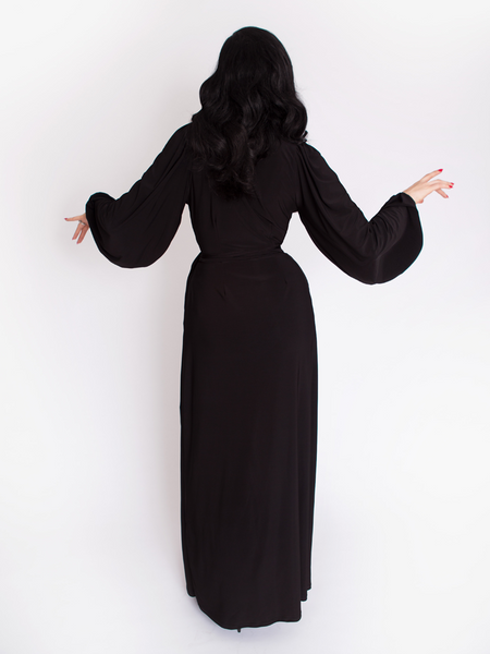 Back shot of Micheline Pitt wearing the gothic vintage clothing Black Widow Wrap Gown in Solid Black.