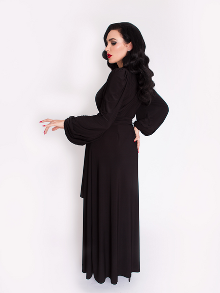 Profile picture of Micheline Pitt wearing the Black Widow Wrap Gown in Solid Black.