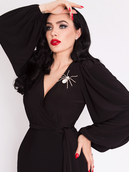Close-up shot of Micheline Pitt wearing the Black Widow Wrap Gown in Solid Black with spider pendant.