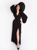 Micheline Pitt photographed while wearing the Black Widow Wrap Gown in Solid Black paired with a oversized black sunhat.