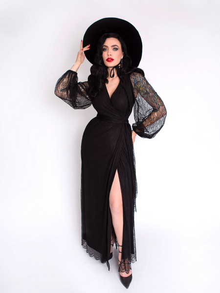 Posing with her leg positioned out in front of her, Micheline Pitt shows off the Black Widow Wrap Gown in Black Lace from La Femme en Noir.