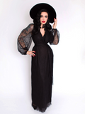 Micheline Pitt wearing the Black Widow Wrap Gown paired with a black sunhat.