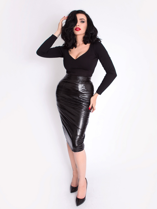 Micheline Pitt models the Black Marilyn Top in Black paired with a black skirt.
