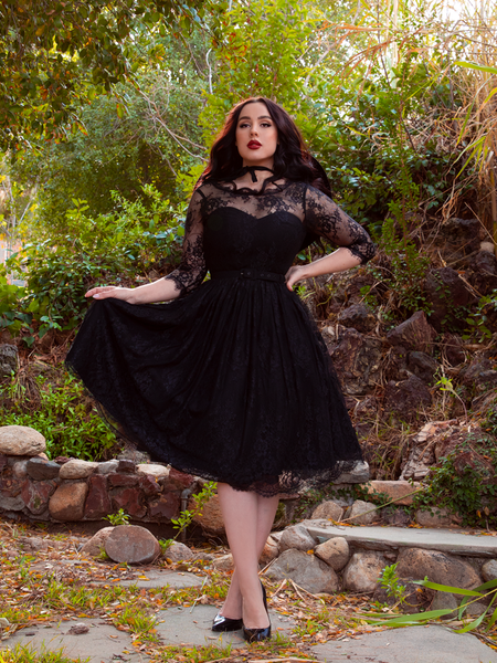 Pulling out the fabric on one side of her Mourning Dress in Black Lace, model Rachel Sedory shows off the intricate lace design of this gothic dress.